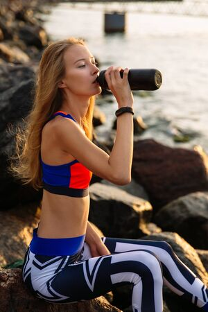 Profile of healthy girl wit long blonde hair, in sportswear, drinking a water from bottle, while sitting on sea stones. Sport concept.