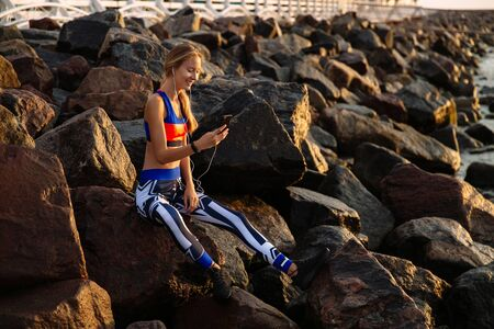Cheerful sportive young woman in headphones, listening to music while using a mobile phone, sitting on sea stones. Dressed on sport leggings and singlet.