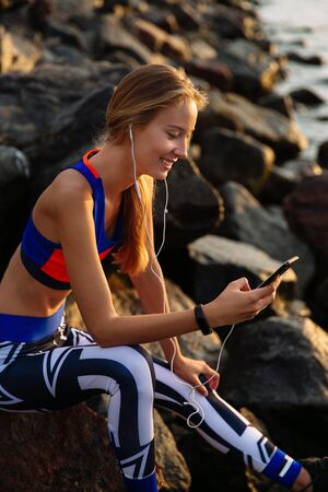 Happy beautiful young woman in earphones, listening to music while using a mobile phone, browsing, sitting on stones, near the sea, wearing sportswear.