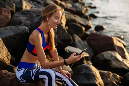 Joyful healthy woman in earphones, listening to music while using a smartphone, browsing, sitting on stones, near the sea, wearing sportswear. Banco de Imagens