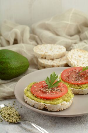 Mashed Avocado Rice Cakes with Sliced Tomato and Sesame Seeds - a healthy breakfast, snack or dinner option