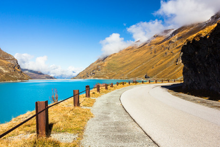 invitando: Inviting road with blue lake on the side. Foto de archivo