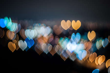 Blurred lights of Kuala Lumpur skyline, love shape bokeh