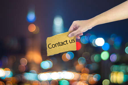 contact us sign: Hand holding a Contact us sign made on sugar paper with city light bokeh as background