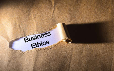 business ethics: torn paper with word business ethics
