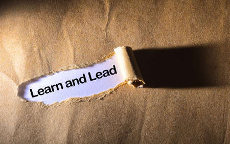 learn and lead: torn paper with word learn and lead Stock Photo