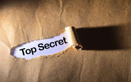 undisclosed: torn paper with word Top Secret Stock Photo