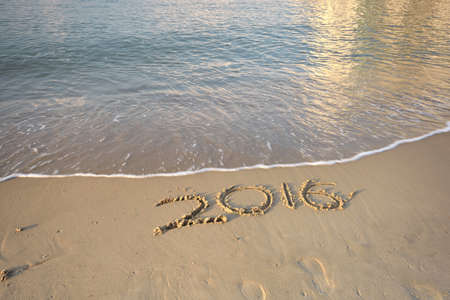 sand drawing: Year 2016 on the beach Stock Photo