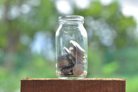putting money in pocket: Jar for savings full of coins.