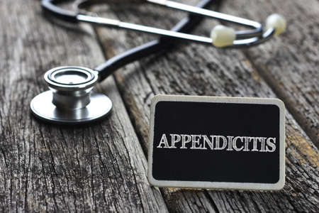 appendix ileum: Medical Concept-APPENDICITIS word written on blackboard with Stethoscope on wood background