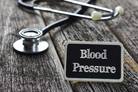 young  cuffs: Medical Concept- Blood Pressure word written on blackboard with Stethoscope on wood background Stock Photo