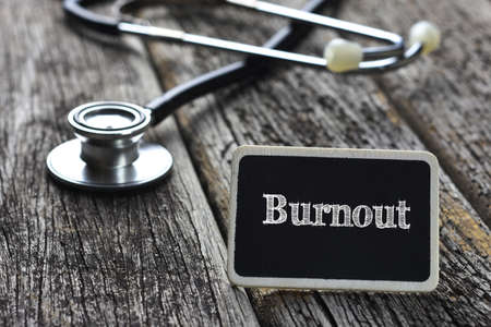 burnout: Medical Concept- Burnout word written on blackboard with Stethoscope on wood background