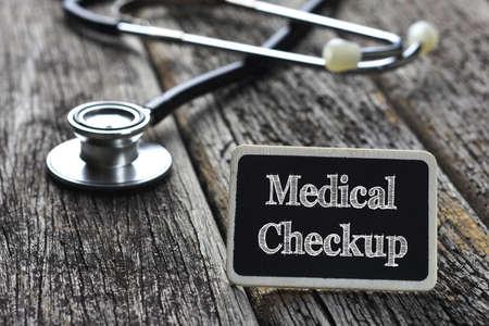 medical checkup: Medical Concept- Medical Checkup  word written on blackboard with Stethoscope on wood background Stock Photo
