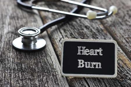heart burn: Medical Concept- Heart Burn word written on blackboard with Stethoscope on wood background Stock Photo