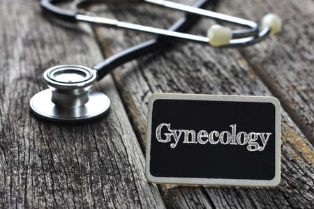 gynecology: Medical Concept- Gynecology word written on blackboard with Stethoscope on wood background