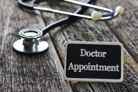 Medical Concept-Doctor Appointment word written on blackboard with Stethoscope on wood background