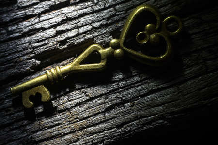 Golden key on rusty wooden table with hard shadow