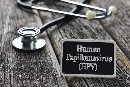 Medical Concept- Human Papillomavirus (HPV) word written on blackboard with Stethoscope on wood background Foto de archivo