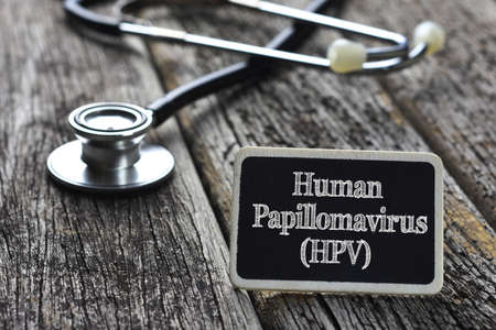 Medical Concept- Human Papillomavirus (HPV) word written on blackboard with Stethoscope on wood background Archivio Fotografico