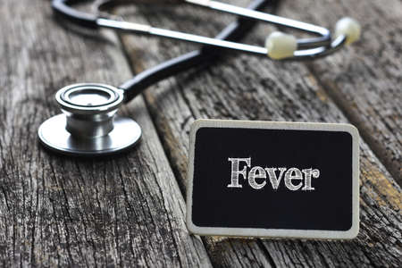Medical Concept-Fever word written on blackboard with Stethoscope on wood background