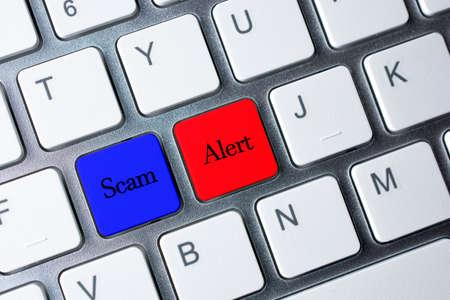 cyber terrorism: Scam Alert button on white computer keyboard