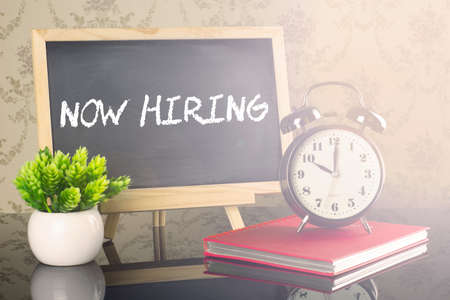 NOW HIRING on blackboard with clock and flare