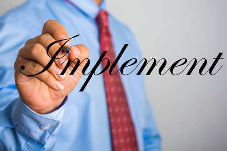 Businessman writing Implement word on virtual screen. Stock Photo