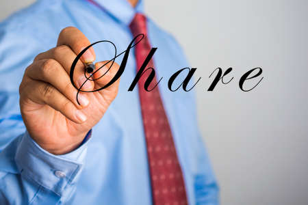 Businessman writing Share on virtual screen. Stock Photo
