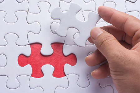 Hand holding piece of blank jigsaw puzzle with red background.