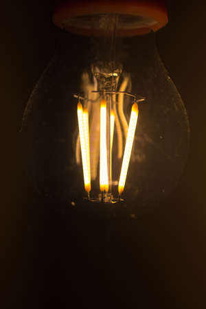 Light bulb is glowing in the dark. Retro background with copy space.