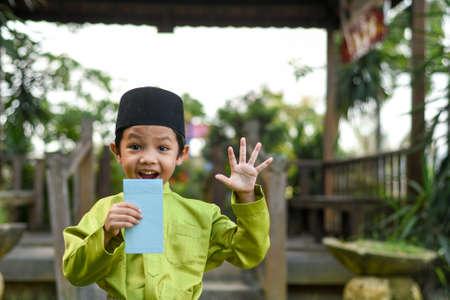 Een Maleisische jongen in Maleisische traditionele kleding die zijn gelukkige reactie toont nadat hij geld heeft ontvangen tijdens de viering van Eid Fitri of Hari Raya.