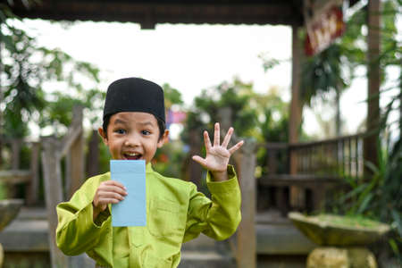Un garçon malais en tissu traditionnel malais montrant sa réaction heureuse après avoir reçu une poche d'argent lors de la célébration de l'Aïd Fitri ou de Hari Raya. Banque d'images - 102639553