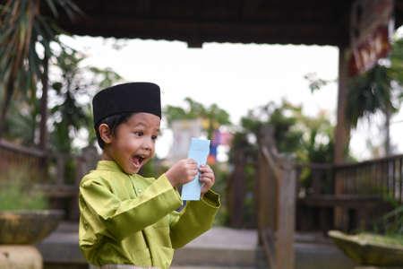 Un garçon malais en tissu traditionnel malais montrant sa réaction heureuse après avoir reçu une poche d'argent lors de la célébration de l'Aïd Fitri ou de Hari Raya. Banque d'images - 102639554