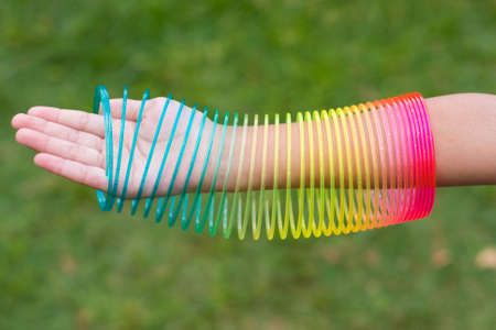 Children playing with rainbow colored wire spiral toy