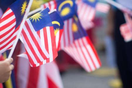 독립 기념일 또는 메르 데카 기념일과 함께 Jalur Gemilang으로도 알려진 말레이시아 국기를 손으로 흔들며.