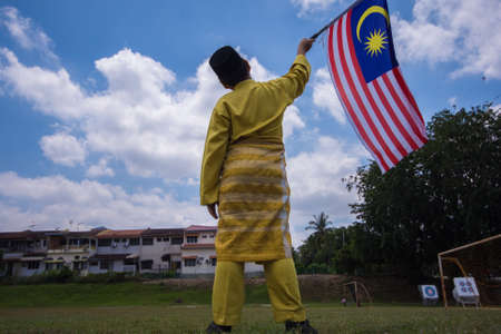 Boy with traditional shirt waving the Malaysia Flag. Independence Day concept. Blue sky and copy space for text.