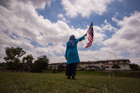 Girl waving the Malaysian flag. Independence Day concept. Blue sky and copy space for text.