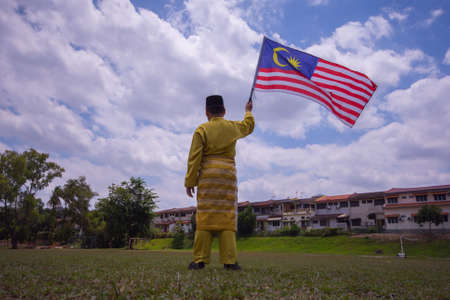 A boy with traditional shirt waving the Malaysia Flag. Independence Day concept. Blue sky and copy space for text. Stock Photo