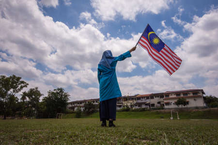Girl waving the Malaysia Flag. Independence Day concept. Blue sky and copy space for text. Stock Photo