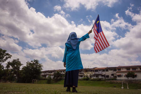 Girl waving the Malaysia Flag. Independence Day concept. Blue sky and copy space for text