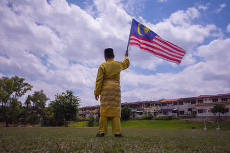 Boy with traditional shirt waving the Malaysia Flag. Independence Day concept. Blue sky and copy space for text Stock Photo