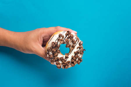 Hand holding delicious glazed doughnuts with choclate cereal topping on color background