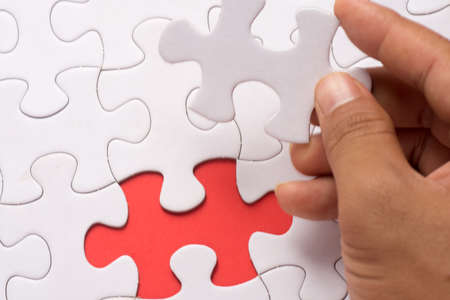 Blur image of close up of hand placing the last jigsaw puzzle piece Stock Photo