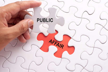 Hand holding piece of jigsaw puzzle with word PUBLIC AFFAIR Stock Photo
