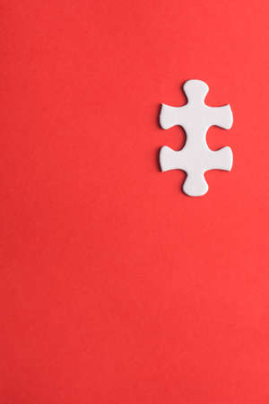 Unfinished white jigsaw puzzle pieces on red background