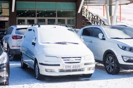SEOUL, SOUTH KOREA - DECEMBER 10, 2018: Vehicles are parked on the street and covered with large amount of snow