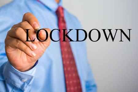 Businessman writing LOCKDOWN on virtual screen