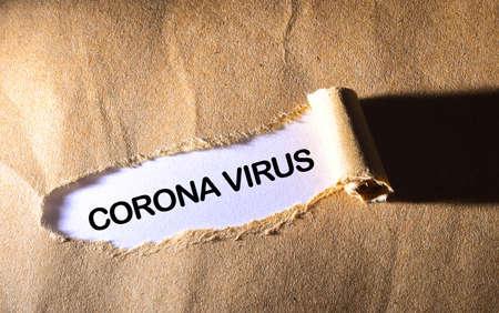 Torn paper with word CORONA VIRUS