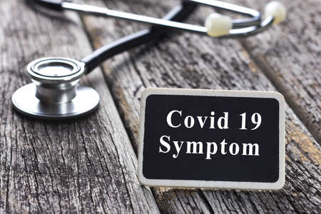 COVID 19 SYMPTOM word written on blackboard with Stethoscope on wood background Standard-Bild