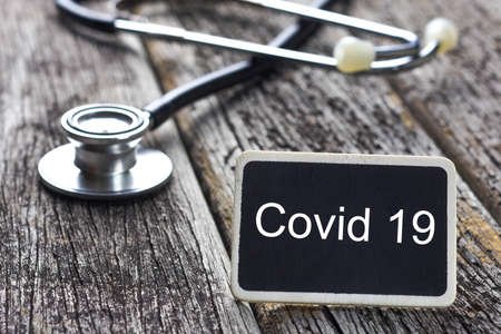 Medical Concept-Covid 19 word written on blackboard with Stethoscope on wood background Archivio Fotografico